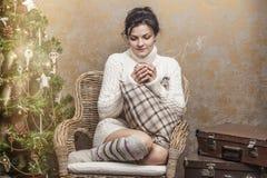 Chá bebendo ou café da mulher bonita que sentam-se em uma cadeira no Imagens de Stock