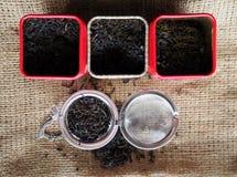 Chá cinzento da mistura do conde com seus ingredientes do sabor do chá preto e da bergamota em umas caixas da lata na lona da jut Imagem de Stock