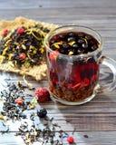 Chá com bagas e pétalas na tabela Imagem de Stock Royalty Free