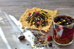 Chá com bagas e pétalas na tabela Fotografia de Stock Royalty Free