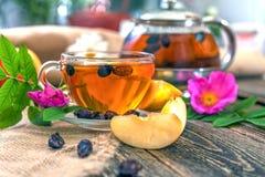 Chá com cão-rosa secada e maçã em uma tabela de madeira Fotografia de Stock Royalty Free