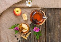 Chá com cão-rosa secada e maçãs em uma tabela de madeira Fotos de Stock