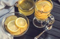 Chá com gengibre e limão em um copo de vidro e em uns doces amarelos Imagens de Stock Royalty Free
