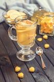 Chá com gengibre e limão em um copo de vidro e em uns doces amarelos Foto de Stock