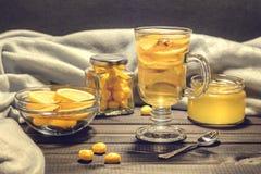 Chá com gengibre e limão em um copo de vidro e em uns doces amarelos Foto de Stock Royalty Free