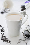 Chá com leite em copo branco rachado da porcelana com gato Imagem de Stock Royalty Free