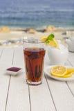 Chá com limão e canela na praia foto de stock royalty free