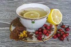 Chá com limão em um copo branco Bagas vermelhas na tabela imagem de stock