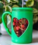 Chá com morangos potenciômetro com coração de vidro Close-up fotos de stock