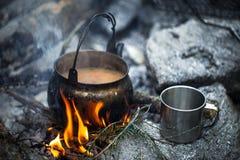 Chá com o leite cozinhado na estaca Uma chaleira, uma caneca do metal, um fogo imagem de stock royalty free