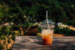Chá congelado do leite com palha na tabela de madeira Foto de Stock