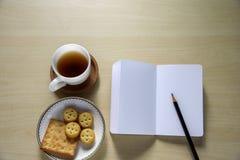 Chá, cookies e livro de nota na tabela Fotos de Stock Royalty Free
