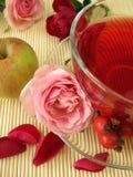Chá da fruta com quadris cor-de-rosa, maçãs e as flores cor-de-rosa Foto de Stock