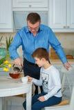 Chá da manhã O pai derrama o chá imagens de stock royalty free