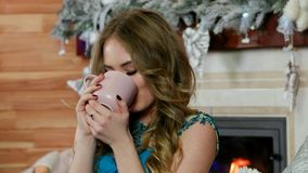 Chá da menina alegre ou café bebendo, uma mulher em um bom humor que olha a câmera, guardando um copo da bebida quente, sorrindo, vídeos de arquivo