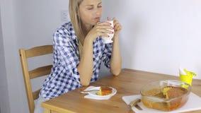 Chá da mulher e comer em sua cozinha torta bebendo em casa video estoque