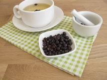 Chá das bagas de zimbro e bagas de zimbro secadas Imagem de Stock