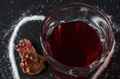 Chá das bagas no vidro, açúcar derramado na forma do coração ao redor, chocolate de leite Imagens de Stock