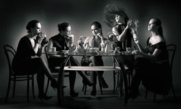 Chá de cinco meninas da beleza que bebe na tabela imagens de stock