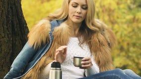 Chá de derramamento da menina da garrafa térmica, apreciando a bebida quente na floresta do outono, conforto filme