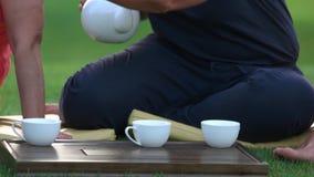 Chá de derramamento da mulher ascendente próxima em uns copos fora filme