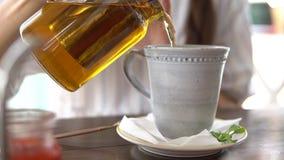 Chá de derramamento da mulher do bule no copo vídeos de arquivo