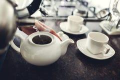 Chá de derramamento da mulher no copo cerâmico na tabela foto de stock