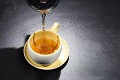 Chá de derramamento em um copo foto de stock