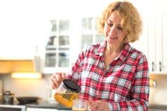 Chá de derramamento envelhecido médio da mulher foto de stock