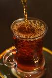 Chá de derramamento no vidro Imagem de Stock Royalty Free
