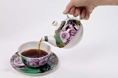 Chá de derramamento usando o jogo de chá decorado Fotografia de Stock Royalty Free