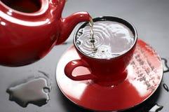 Chá de fluxo no copo vermelho Foto de Stock
