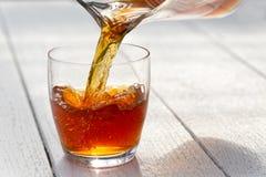 Chá de gelo de derramamento de um jarro de vidro em um vidro Backgr de madeira branco foto de stock royalty free