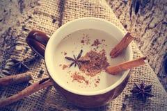 Chá de Masala chai com especiarias e anis de estrela, vara de canela, grãos de pimenta, no saco e no fundo de madeira Foto de Stock