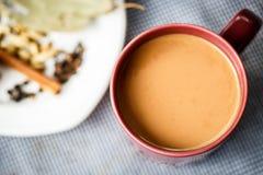 Chá de Masala com as especiarias na tabela imagens de stock royalty free