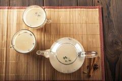 Chá de Masala em um fundo de madeira estrutural Um bule é um potenciômetro transparente do chá com canecas e o masala nacional in fotografia de stock