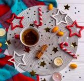 Chá, decoração do Natal, varas de canela, confetes das estrelas no fundo branco da tabela fotografia de stock royalty free