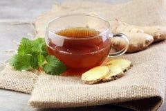 Chá do gengibre com hortelã e limão no fundo cinzento Imagem de Stock
