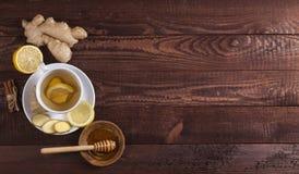 Chá do gengibre com limão, canela e mel no fundo de madeira fotografia de stock