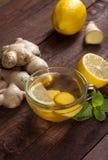 Chá do gengibre com limão, hortelã e mel no fundo de madeira fotografia de stock