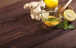 Chá do gengibre com limão, hortelã e mel no fundo de madeira foto de stock