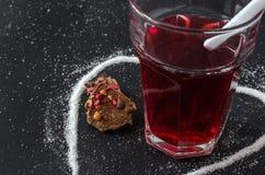 Chá e colher das bagas no vidro, açúcar derramado na forma do coração Imagens de Stock Royalty Free