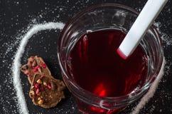 Chá e colher das bagas no vidro, açúcar derramado na forma do coração ao redor Foto de Stock Royalty Free