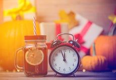 Chá e despertador ao lado da abóbora com caixa de presente de Dia das Bruxas Imagens de Stock Royalty Free