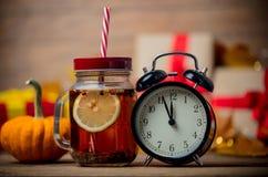 Chá e despertador ao lado da abóbora com caixa de presente de Dia das Bruxas Imagem de Stock Royalty Free