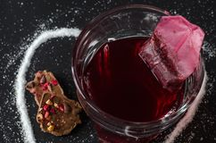 Chá e saquinho de chá da morango no vidro, açúcar derramado na forma do coração ao redor Fotografia de Stock