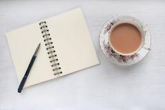 Chá em um copo e uns pires do vintage, e caderno com páginas vazias Fotos de Stock Royalty Free