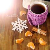 Chá em uma caneca envolvida no lenço minúsculo cercado por segmentos do mandarino Fotografia de Stock