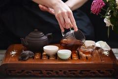 Chá em umas bacias, em um bule da argila e nas mãos humanas derramando o chá Foto de Stock