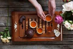 Chá em umas bacias, em um bule da argila e nas mãos humanas guardando a bacia Fotografia de Stock